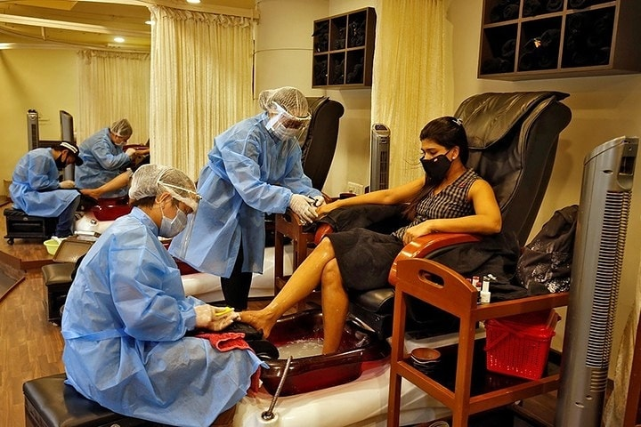 Beauticians wearing protective gear tend to their customers inside a parlor at a shopping mall after authorities allowed the reopening of malls, during an extended nationwide lockdown to slow the spreading of the coronavirus disease (COVID-19), in Ahmedabad, India, June 8, 2020⁣ ⁣ 📸: Amit Dave​/Reuters​  Source: Forbes India